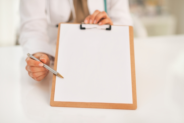 Closeup on happy medical doctor woman pointing in clipboard