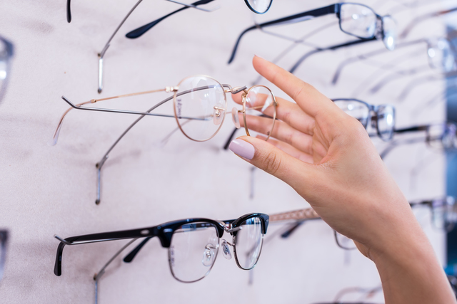 Woman taking glasses out of shelf in optician store, close up on hand